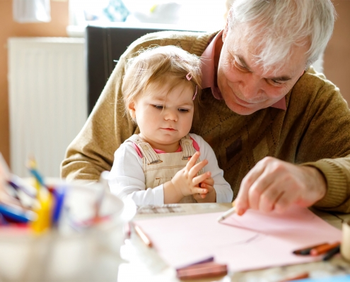 elderly man drawing a picture with a baby